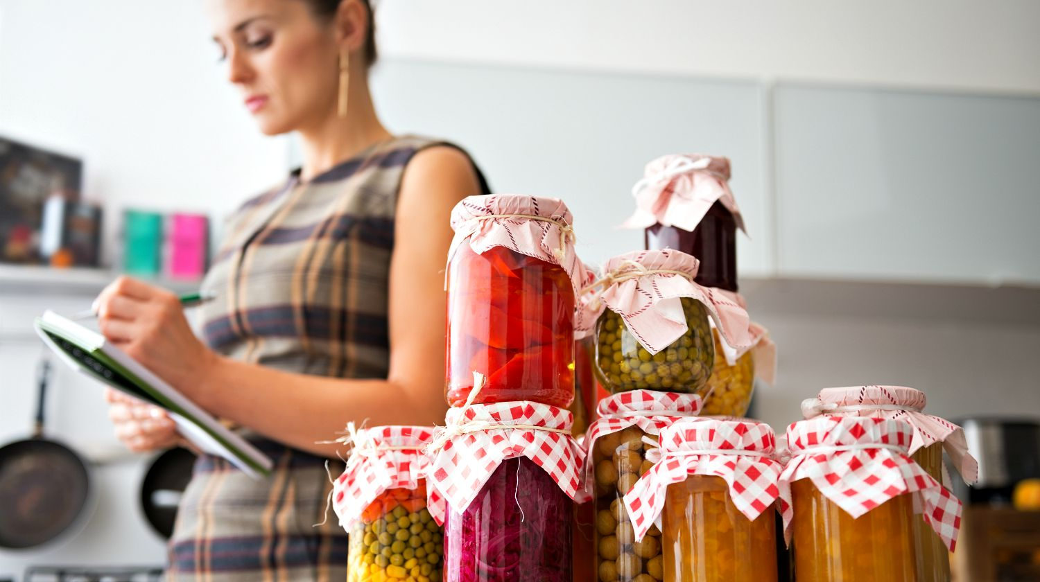 Featured | Housewife writing in notepad with jars of homemade fruits jam and pickled vegetables | Items to Kick-Start Your Food Storage Plan