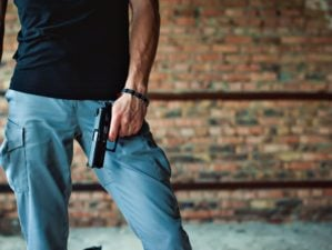 Feature | Dangerous athletic man holding a gun in his hand | Concealed Carry Tips For Gun Owners | Best Gun Concealment