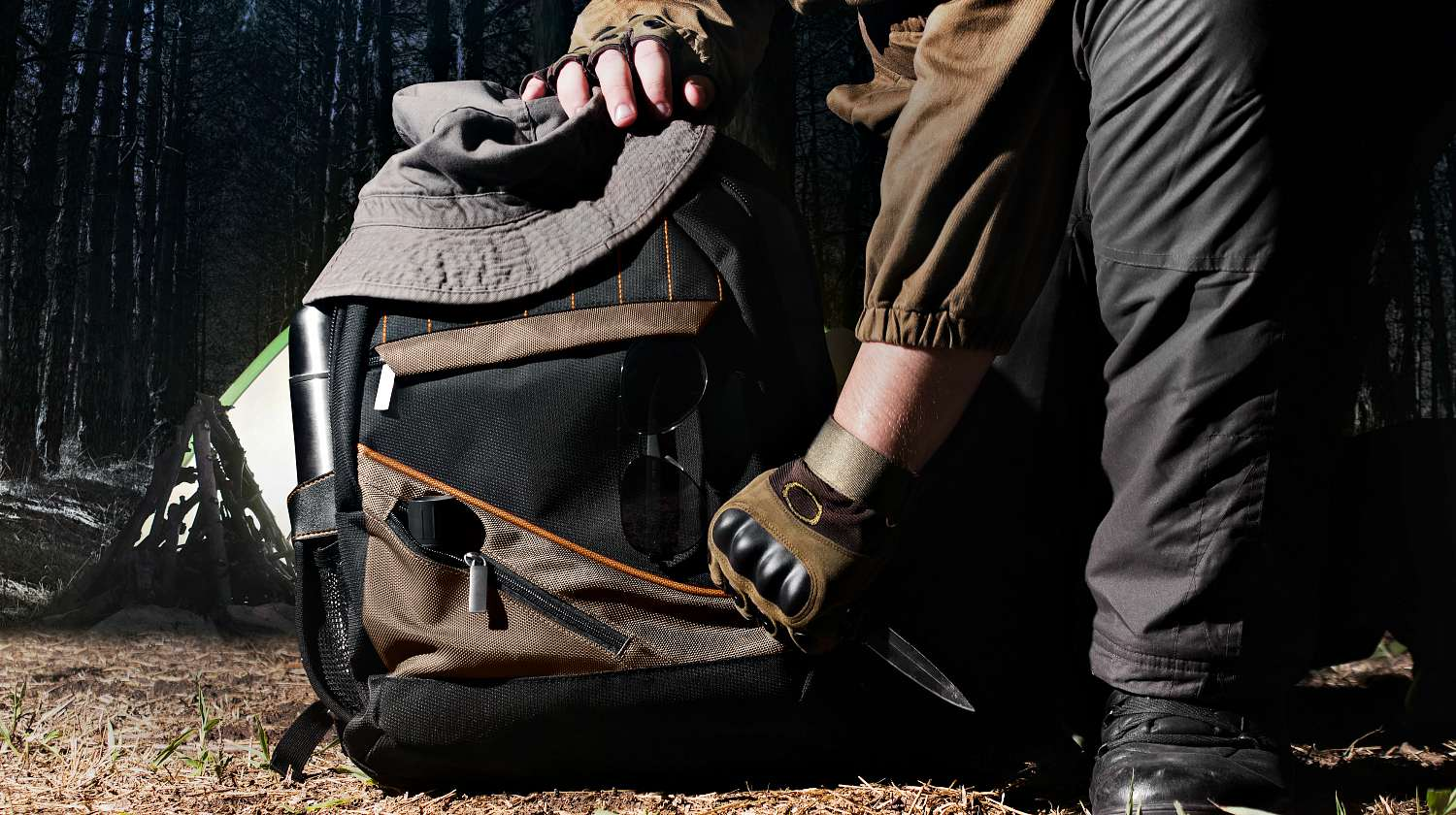 Featured   Man in tactical outfit holding a knife and kneeling for backpack with camping and tactical gear on night forest background   How To Fix Backpack Straps And Zippers Outdoors
