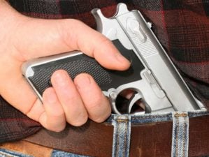 Pistol concealed in a man's waistband | No-Permit Concealed Carry Now Allowed In Maine | Featured
