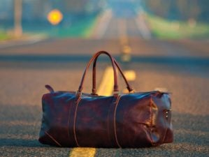 Feature | A brown leather duffel bag in middle on gray asphalt road | Preparedness Tips: Prepping For Travel