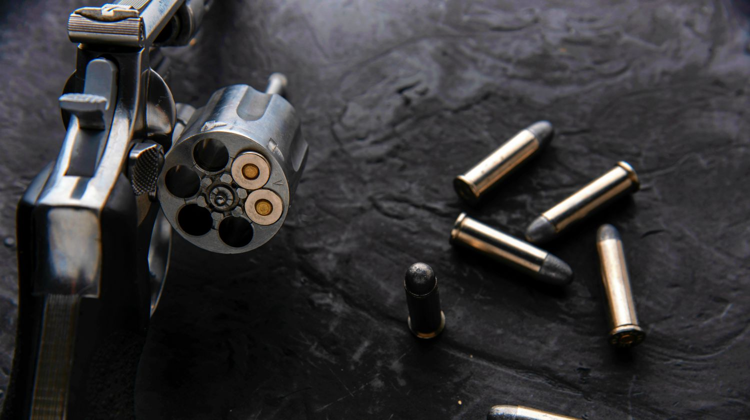 Gun with ammunition on dark background | Bringing Gun To The Gym: Why And How To Concealed Carry At The Gym | Featured