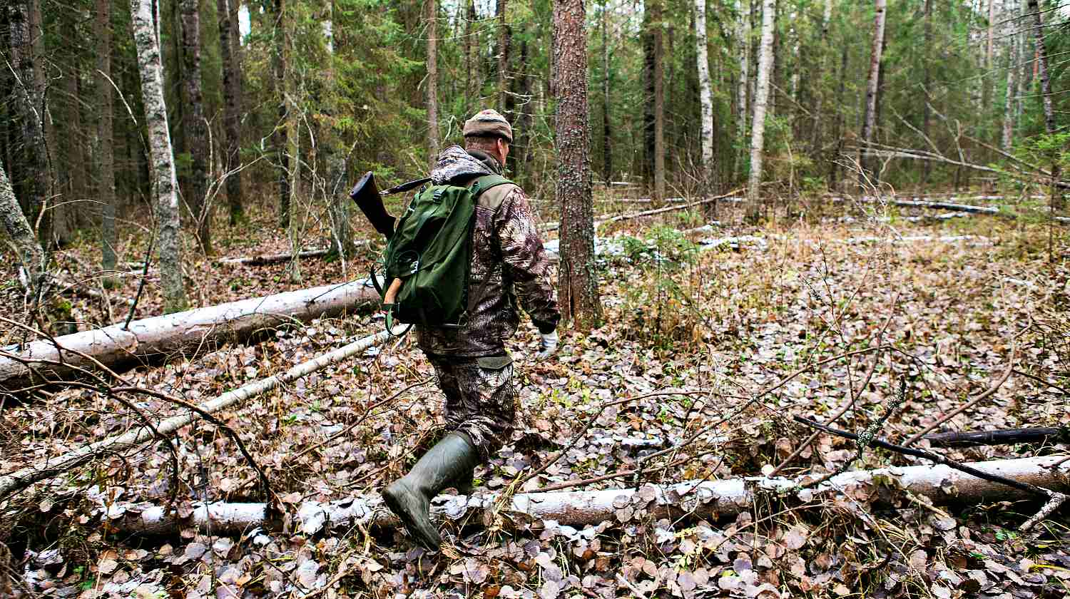 Man the hunter goes through the forest in rubber boots, with a backpack and a gun | Go Bag Guns | Getting Your Firearms In Order When SHTF | Featured