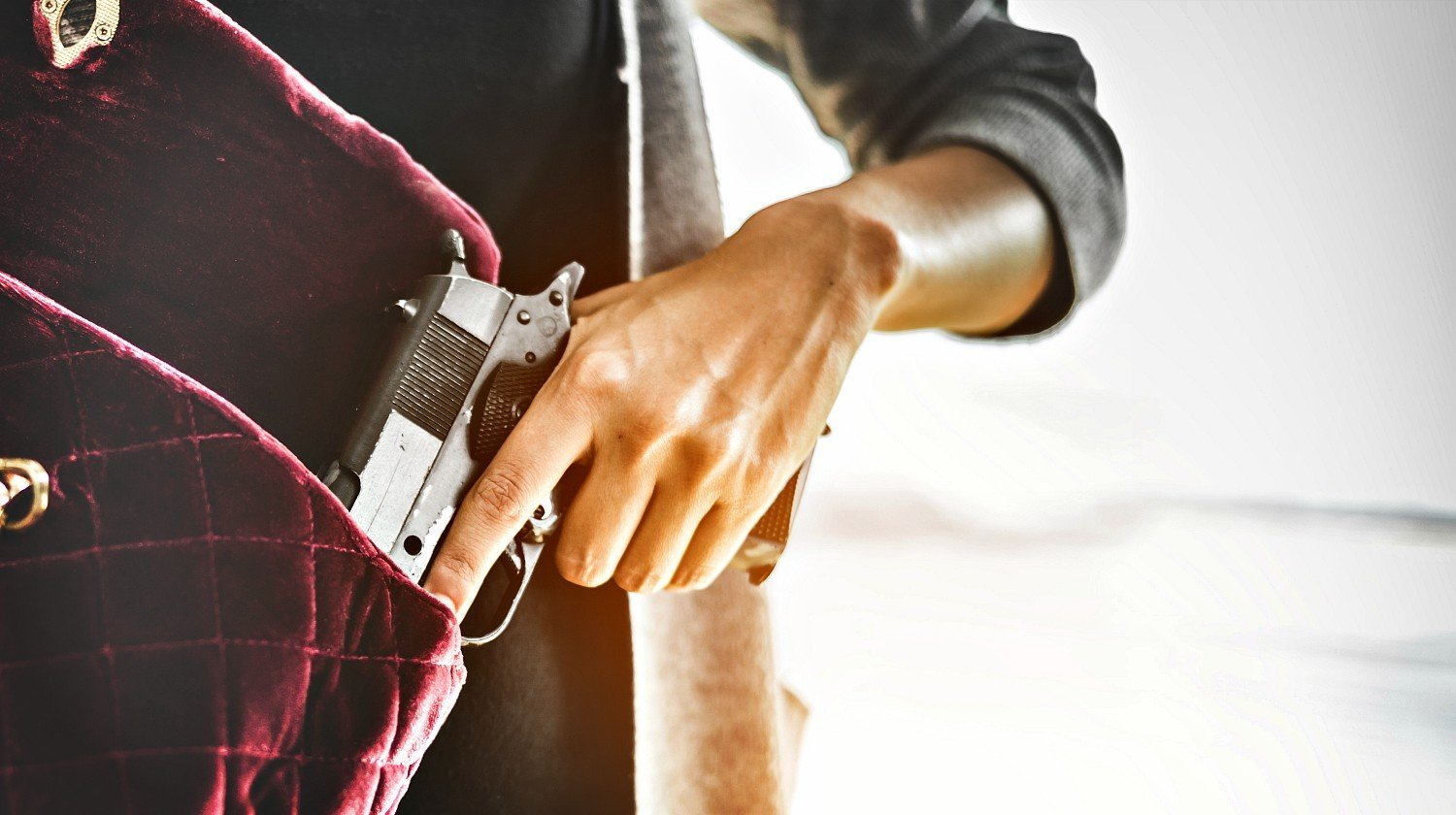 Feature   Woman holds a gun inside her bag   The Best Concealed Carry Guns For Women