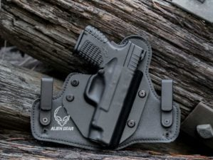 Feature   Black handgun in the woods   Self-Defense Weapons: Guns You Need For When SHTF