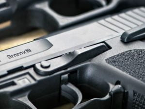 Feature   Three guns on a wooden table   9mm vs .40 vs .45   Which is Better for Self Defense?