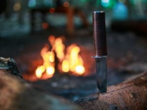 Knife in wood by fire | Best Survival Knife Brands You Can Trust | Featured