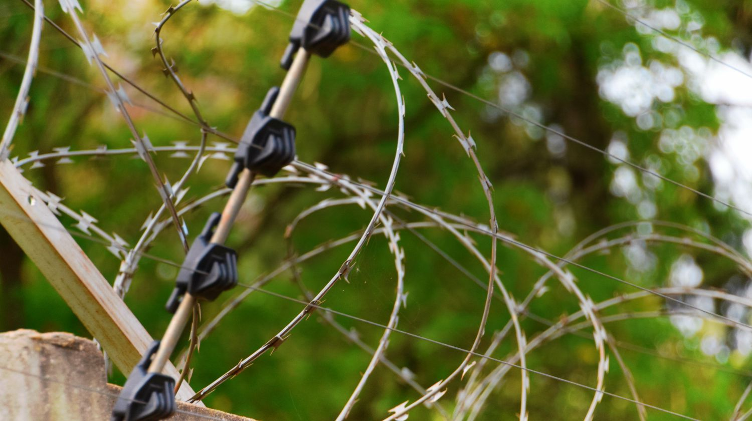 Barbed wire and electric fence wall security   Simple, Low-Tech, High Security Perimeter Alarm   Featured
