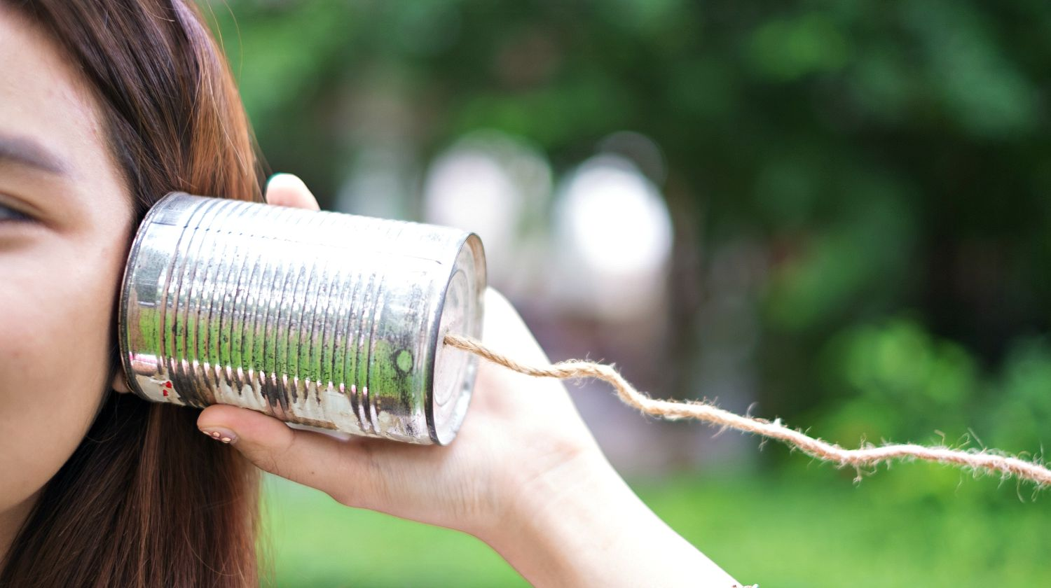 A girl listening through the tin can telephone | Surprising Survival Uses For A Tin Can | Featured