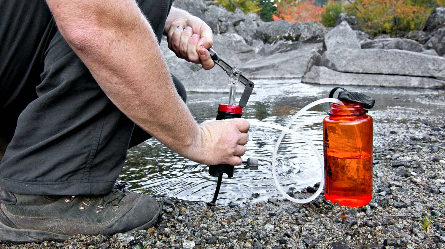 Hiker filtering water from stream | How To Purify Water | Water Decontamination Techniques | Featured