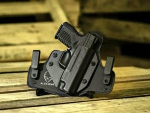 Feature | Automatic handgun with black holster on a wooden background | What's The Best Handgun For Beginners?