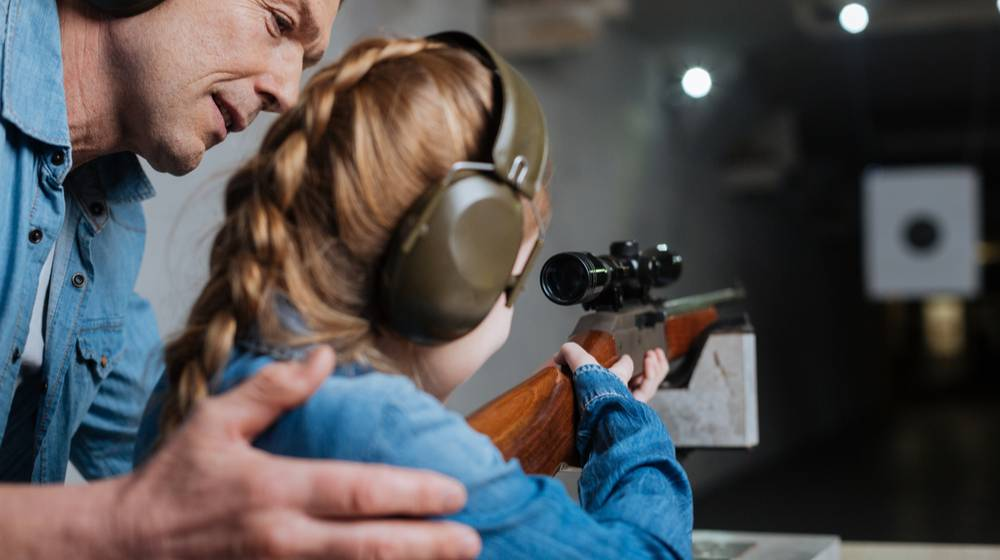 Feature   pleasant-cheerful-man-helping-his-daughter real guns for kids