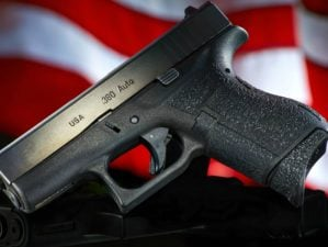 Featured | Handgun on black with flag | Concealed vs Open Carry: Pros And Cons