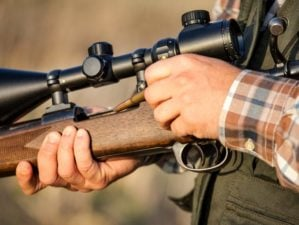 hunter holding rifle | Marlin 336 Review: Is This A Worthy Add To Your Collection? | featured