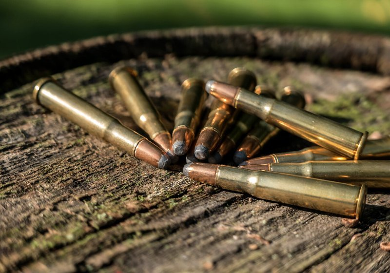 pile bullets on wood winchester 30 | savage axis 350 legend review