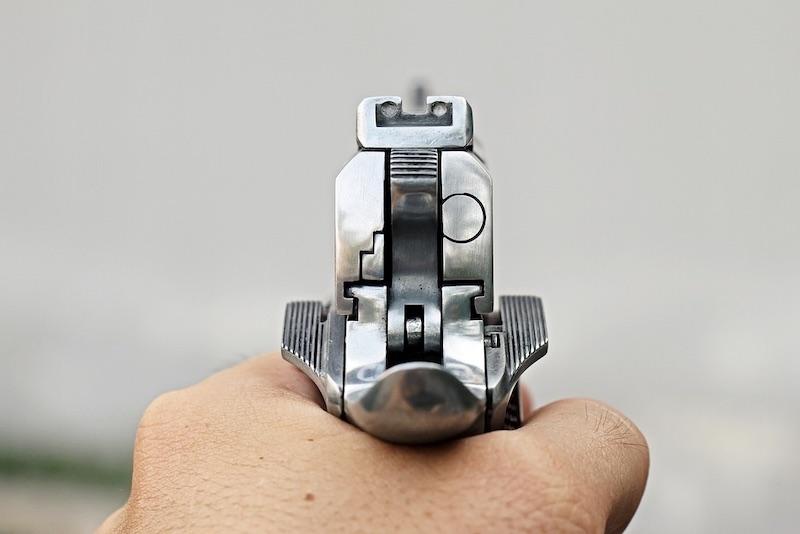 Human hand holding gun, hand aiming a handgun, .45 pistol. | complete dedication