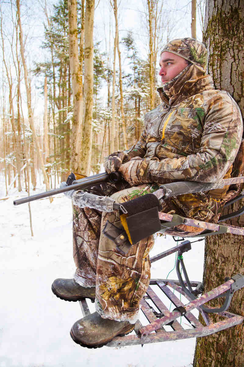 Hunter with rifle in a tree stand | deer hunting gear must haves