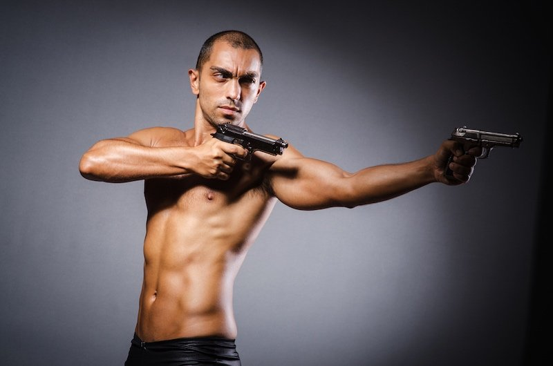 Ripped man with gun against grey background | gear accessories