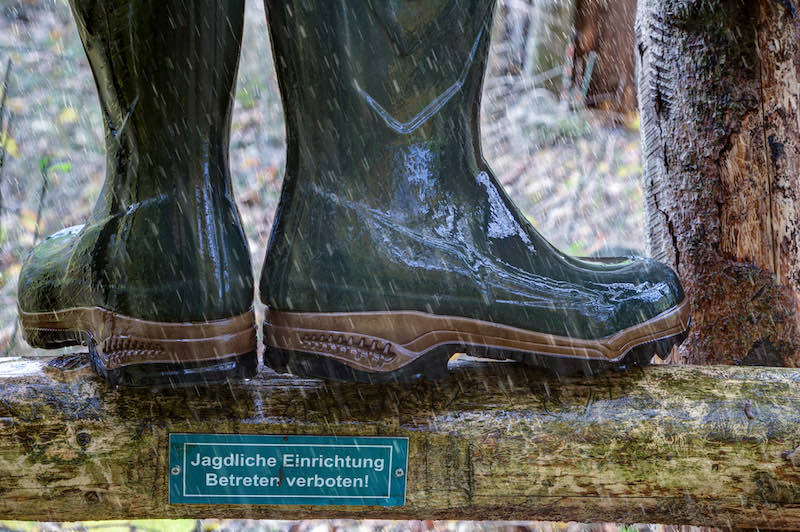 Wellington boots stand in the rain on the wooden ladder of a hunting pulpit | deer hunting checklist excel