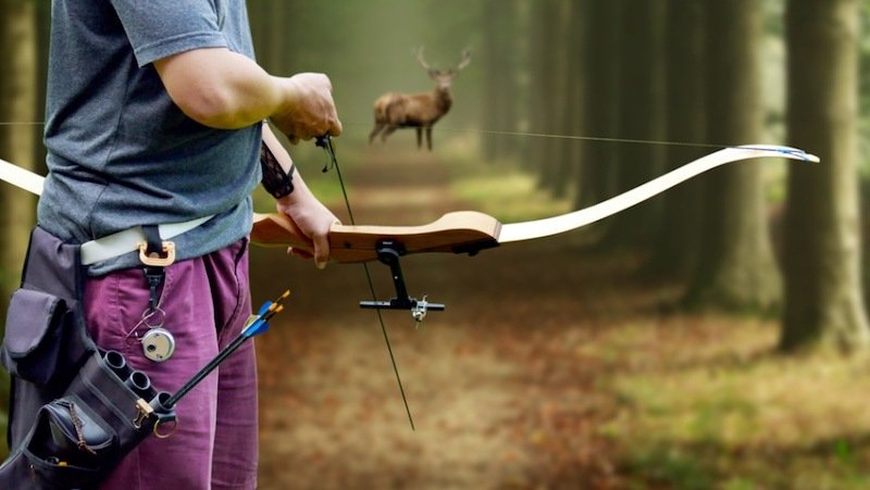a bow hunter aiming at a White tail buck against | traditional muzzleloader