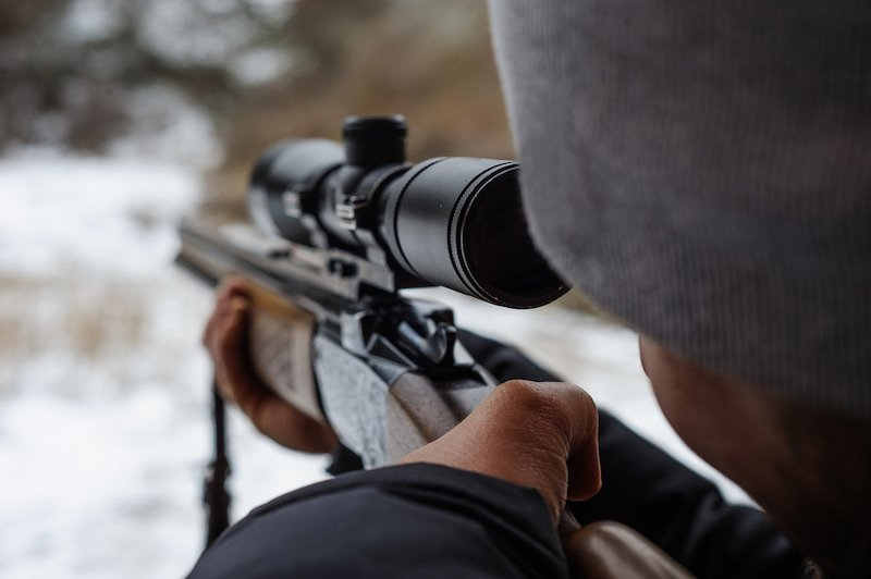 Man holding a sniper and shooting | henry survival rifle