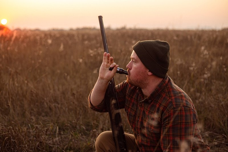 Young red bearded hunter sitting it grass and blowing at hunter's whistle | essential hunting clothes