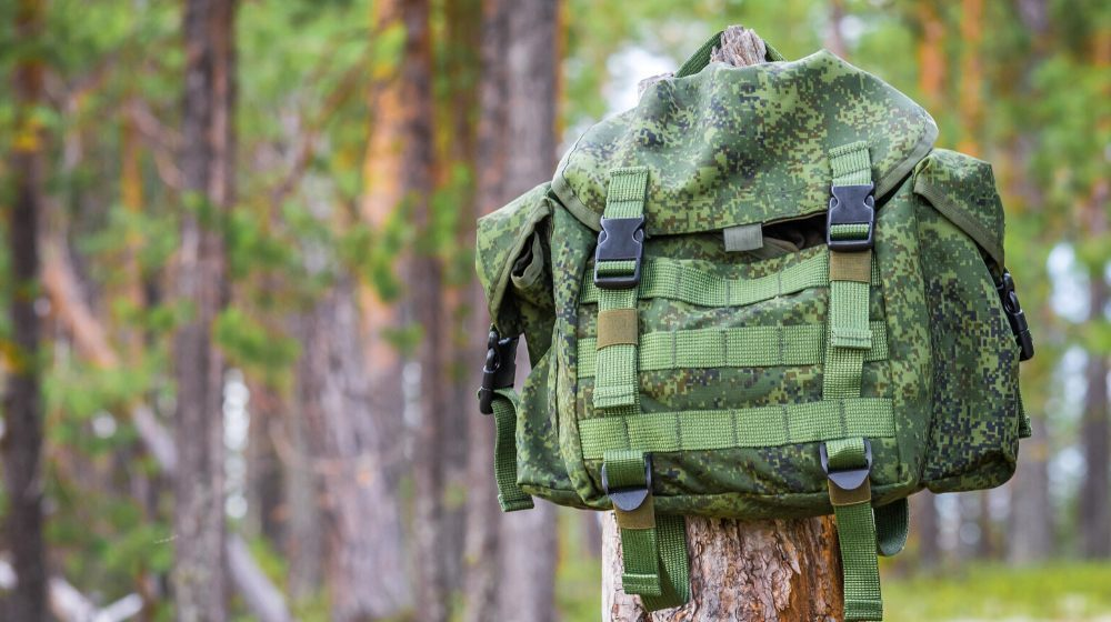 small backpack hanging on trunk tree   How To Turn Your Bug Out Bag Into A Minimalist Backpack   featured