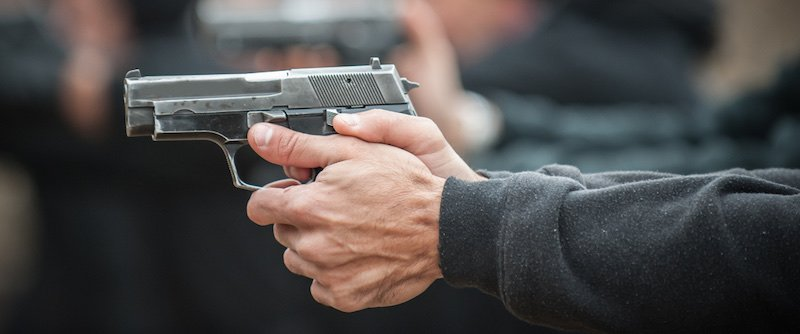 Detail view of left hand shooter shooting and holding gun | ruger mark iv lite
