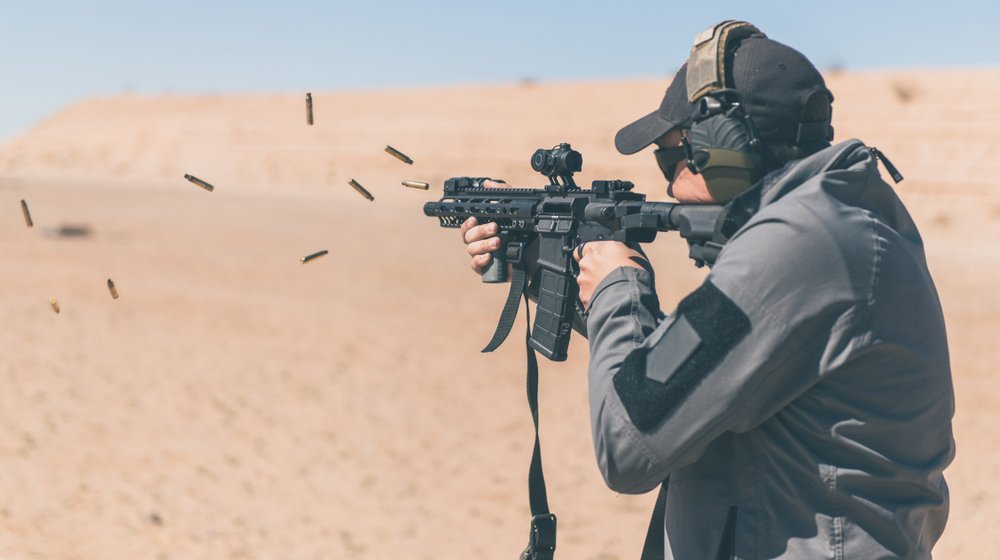 Man with gray jacket shooting black rifle | How to Use an AR-15 | featured