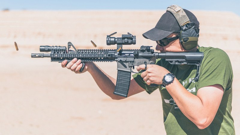 Man with green shirt shooting black rifle on range | how to use an ar 15 for home defense