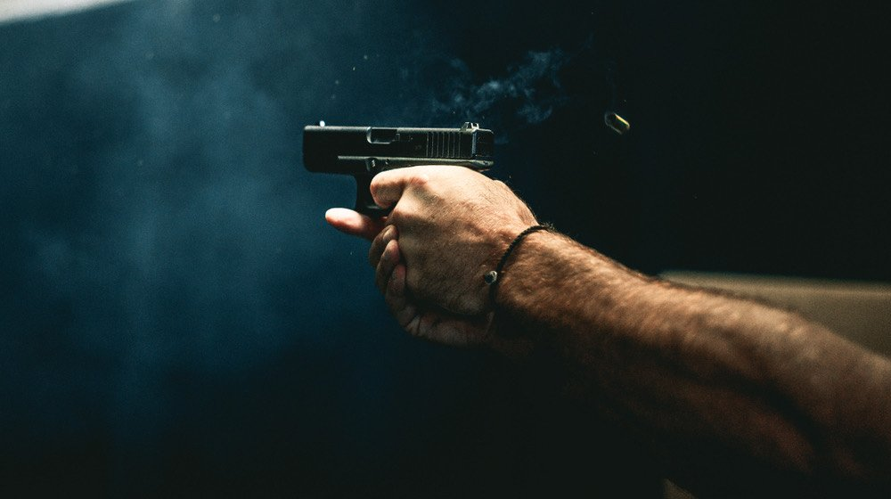close up on a guy shooting firearm handgun   What's the Difference Between Full-Size, Mid-Size & Compact Pistols   featured