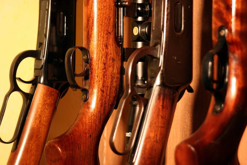 Close up of several rifles inside a weapons cabinet | gun organization