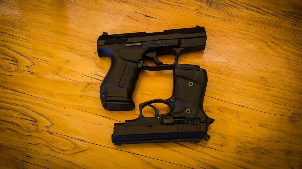 two guns lays on a wooden table | Sig Sauer M18 Vs. Beretta M9A3 Review | featured